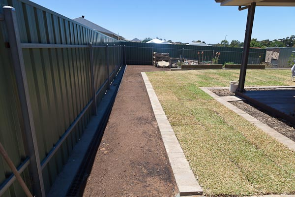 Top soil spread and levelled down the side fence.